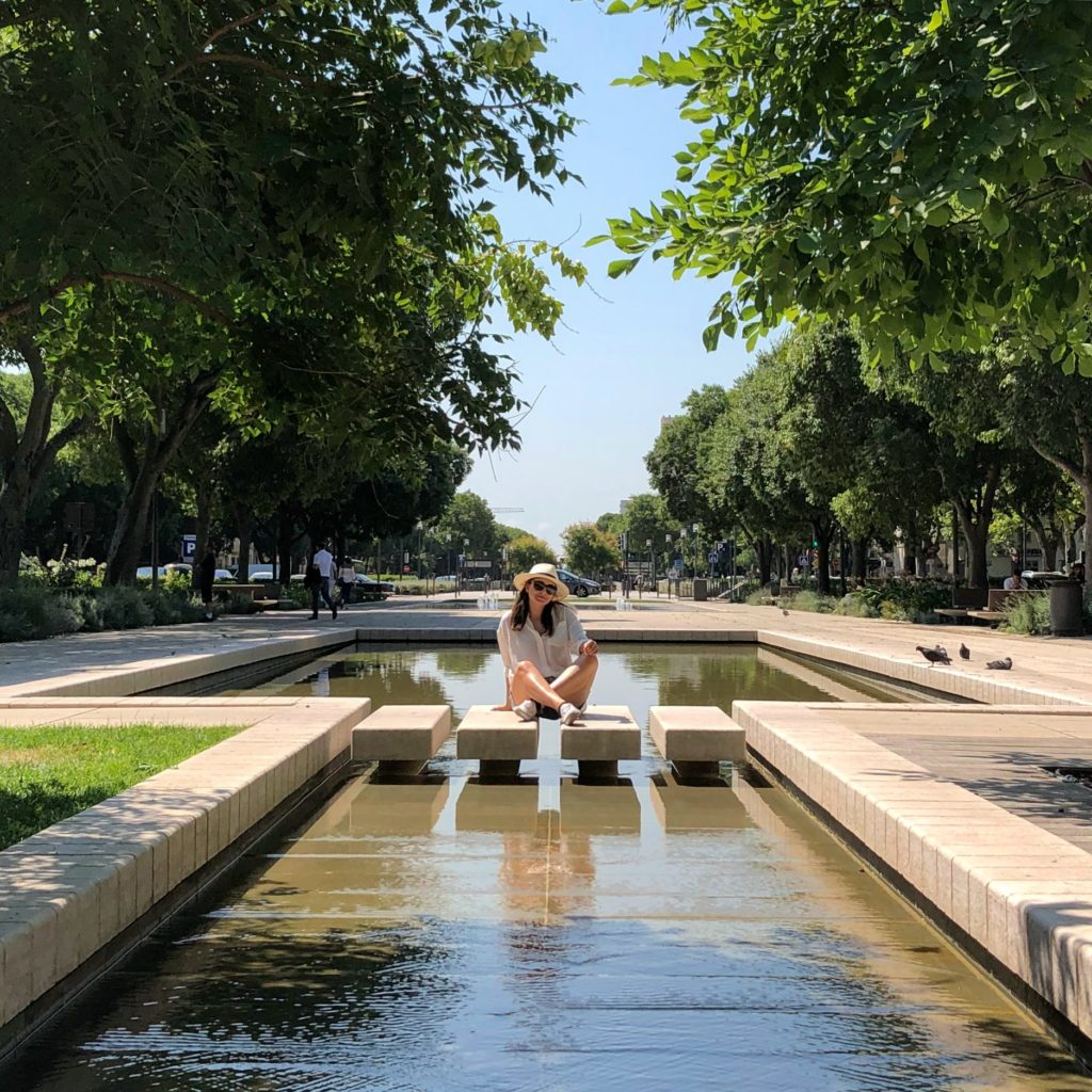 A photo of trees on either side with a woman sitting in the center surrounded by a fountain