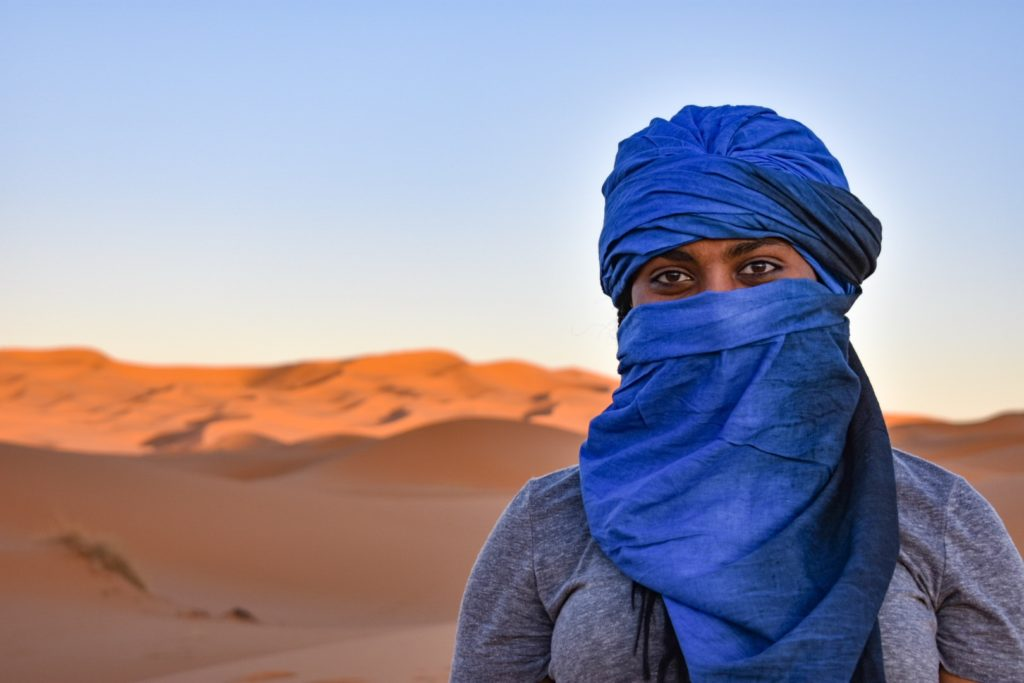 There is a woman who is covered with a blue headscarf with the Sahara desert in the background