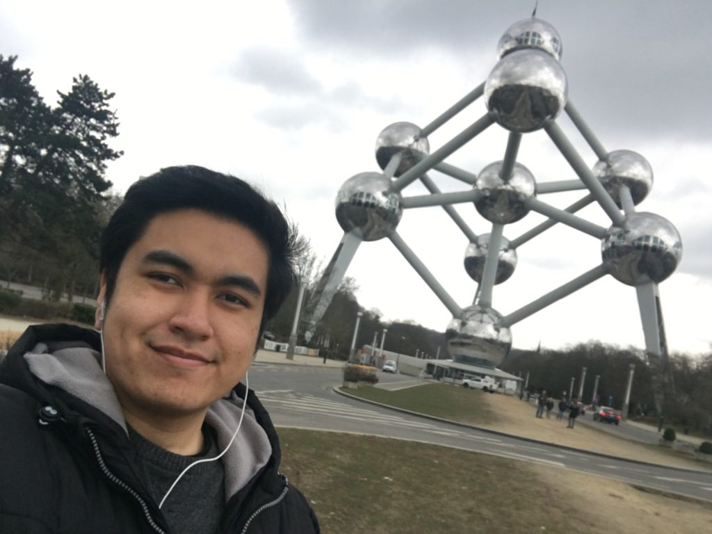 A photo of a man in front of a metallic structure connecting together via round circular objects.